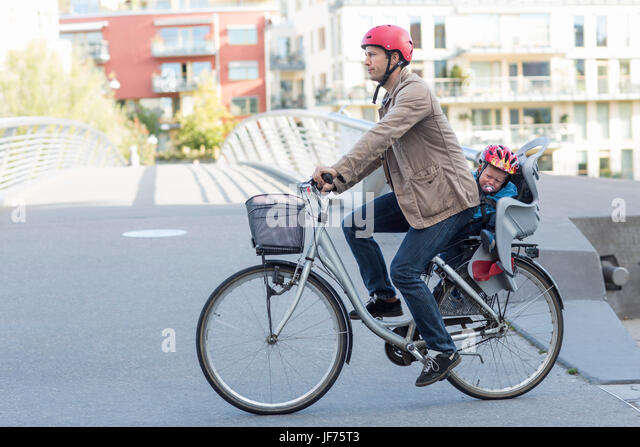 Mann Reiten Fahrrad mit Sohn sitzen im hinteren Sitz Stockbild