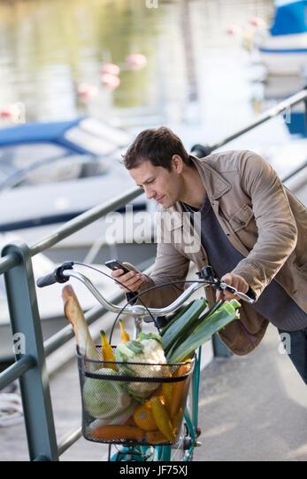 Man lehnt sich auf seinem Fahrrad und SMS auf dem Handy Stockbild