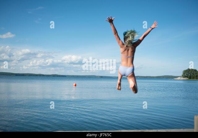 Mädchen See springen Stockbild