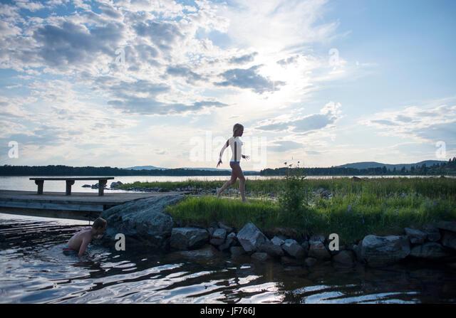 Jungen und Mädchen im See schwimmen Stockbild