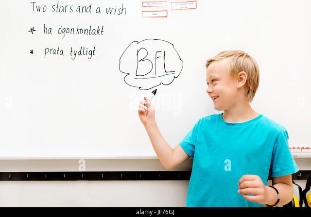 Junge stand vor whiteboard Stockbild