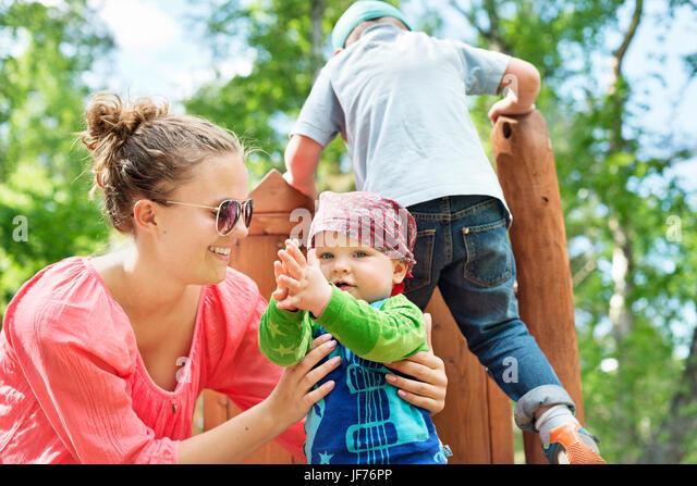 Mutter mit Kindern am Spielplatz Stockbild