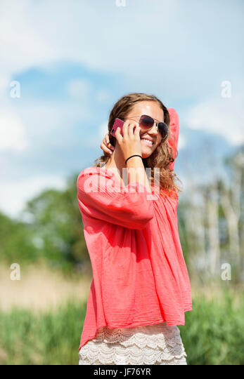 Lächelnde Frau mit Handy Stockbild