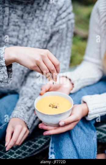 Frau hält eine Schüssel mit Suppe Stockbild