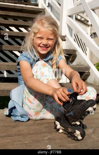 Junges Mädchen binden Fußballschuh Stockbild