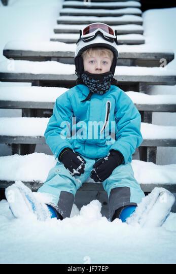 Junge in Skibekleidung sitzen auf Stufen im winter Stockbild