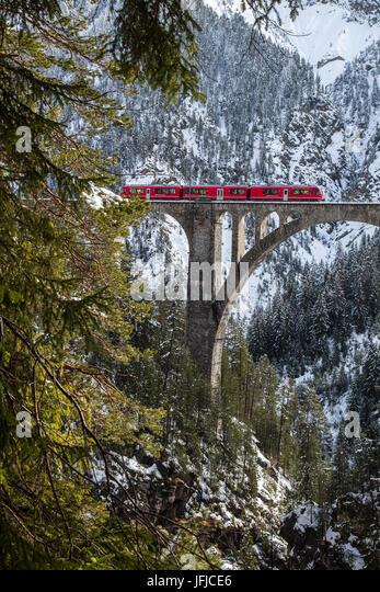 Der rote Zug auf den Wiesener Viadukt umgeben von Wäldern, Engadin, Kanton Graubündens, der Schweiz, Europa, Stockbild