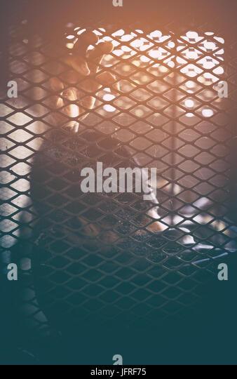 Menschenhandel, Mann in Käfig mit orangem Licht Stockbild