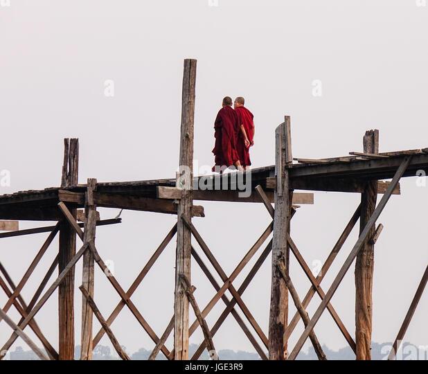 Mönche gehen auf die Ubein Brücke in Mandalay, Myanmar. Ubein wurde um 1850 erbaut und ist vermutlich Stockbild