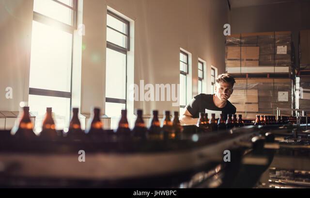 Brewer, Förderband mit Bierflaschen zu betrachten. Junger Mann, Überwachung der Herstellung von Bier im Stockbild