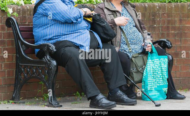 Krankhaft fettleibig. Übergewicht Paar draußen sitzen auf einer Bank. ungesunden Lebensstil. Stockbild