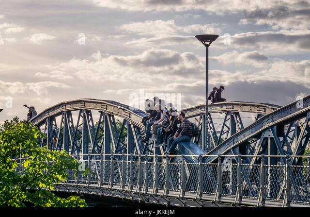 Sonnenuntergang an der blauen Brücke in Freiburg, Menschen sitzen auf Brücke, Freiburg, Baden-Württemberg, Stockbild
