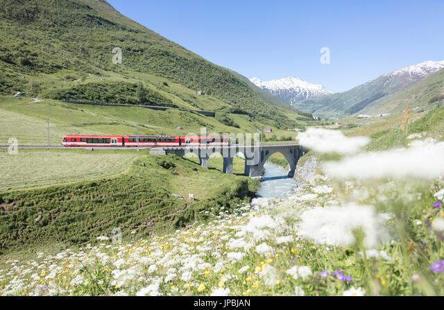 Typische rote Schweizer Schulen an Hospental Viadukt umgeben von Creek und blühenden Blumen Andermatt Kanton Stockbild