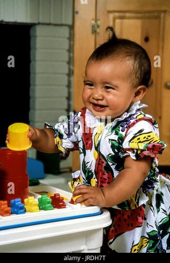18 Monate alten ethnischen Baby Mädchen spielen mit farbigen stapeln Spielzeug Kinder Spaß POV © Stockbild