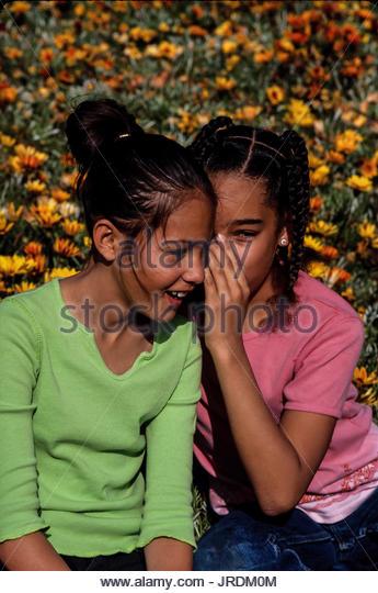 Zwei Mädchen weiterempfehlen Geheimnisse Flüstern in das Ohr von Freund Stockbild