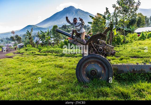 Jungen posieren auf verlassenen Artillerie in der Virunga National Park in der Demokratischen Republik Kongo, Afrika Stockbild