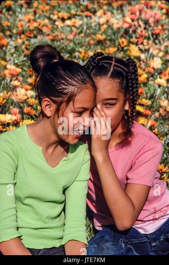 OutdoorsTwo Mädchen weiterempfehlen Geheimnisse Flüstern in das Ohr von Freund © Myrleen Pearson Stockbild