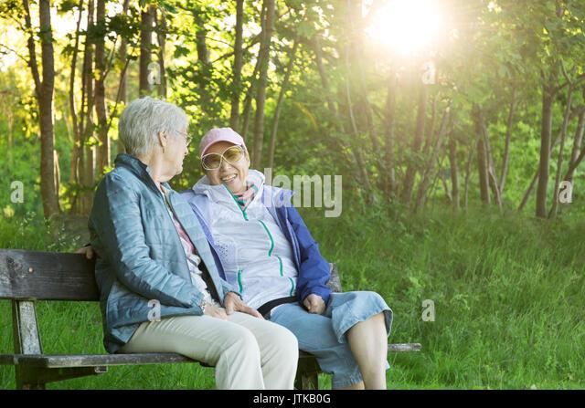 Senior Kaukasischen (Schwedisch) Frau auf einer Parkbank in einem glücklichen Moment mit ihrer asiatischen Stockbild