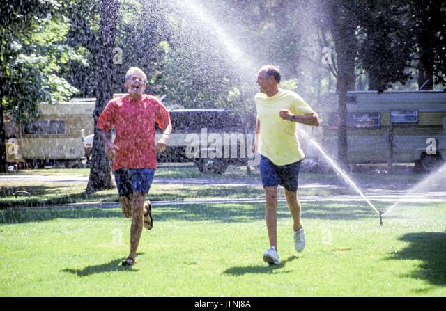 Durch Sprinkler Wasser spielen Arme ausgestreckt liebt das Leben Freiheit aufgeben sorglos Sorglos kindlich verspielter Stockbild