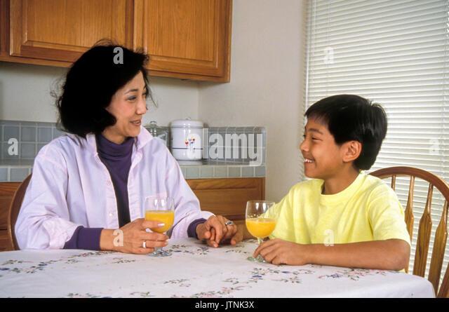 Chinesisch-amerikanische Mutter und Sohn trinken Orangensaft Eltern Kind reden reden unterhalten Myrleen POVy © Stockbild