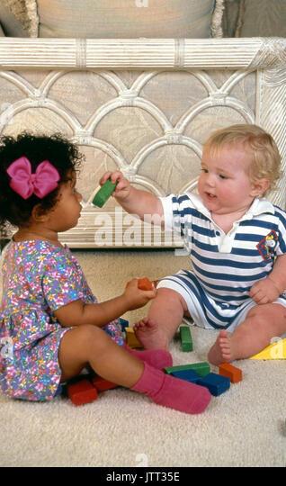 Junge kaukasier Baby sharing gibt Spielzeug block An African American 2-jährige Tochter 18 Monate alten Jungen Stockbild