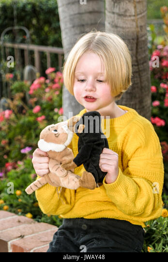 Junge Mädchen spielt die Geschichte mit zwei ausgestopfte Tiere als Zeichen 4-5 Jahre alt im Freien außerhalb Stockbild