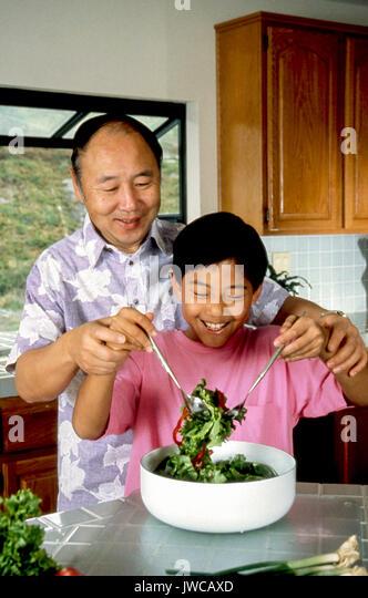 Chinesische Vater und Sohn werfen Salat bereitet sich für Abendessen zusammen Haus innen Stockbild