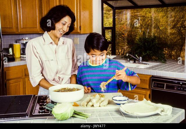 Chinesischen Mutter und Sohn mit Stäbchen Cook Stockbild