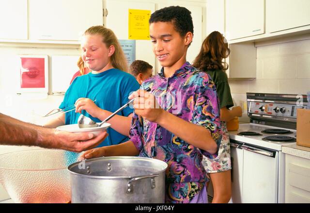 Junge Leute essen, die im Dienst an der Kirche müssen Küche austeilen Essen © Myrleen Pearson Stockbild