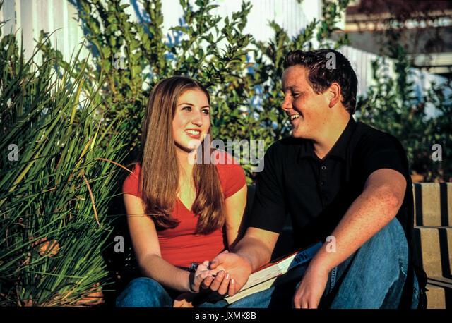 Junge Mensch Leute, junge Teenager Paar lächelnd an einander Sitzen auf Schritte im Vorgarten der Schule. Gesunde Stockbild