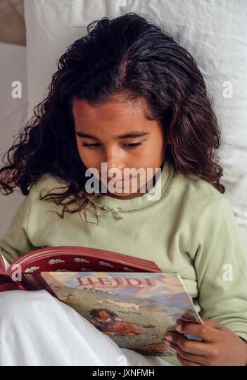Junge Mädchen 7-10 Jahre alten lesen Geschichten bilderbuch Heidi im Bett African American/Kaukasisch interessiert Stockbild