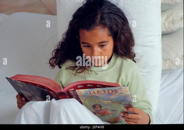 Junge Mädchen 7-10 Jahre alten Lesen storybook im Bett African American/Kaukasisch Stockbild