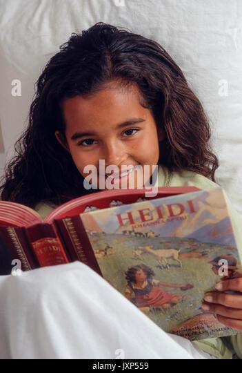 Kleines Mädchen 7-9 Jahre alt mit aufrichtiger Ausdruck lesen klassische Storybook 'Heidi' im Bett Stockbild