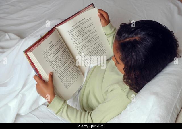 Junge Mädchen 7-10 Jahre alten lesen Buch im Bett African American/Kaukasisch © Myrleen Pearson Stockbild