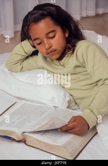 Junge Mädchen 7-10 Jahre alten Lesen der Bibel im Bett African American/Kaukasisch Myrleen Pearson Stockbild