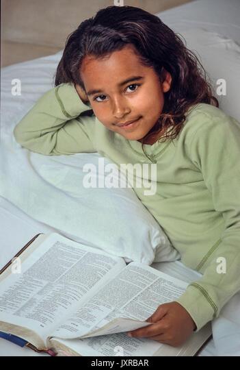 Junge Mädchen 7-10 Jahre altes Kind Lesen der Bibel im Bett African American/Kaukasisch hohen Winkel von oben Stockbild
