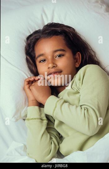 Bedtime für junge Mädchen 7-10 Jahre alten im Bett bereit zu beten und gehen African American/Kaukasischen Stockbild
