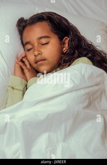 Bedtime für junge Mädchen 7-10 Jahre alten schlafend im Bett friedlichen afrikanischen amerikanischen/Kaukasisch Stockbild