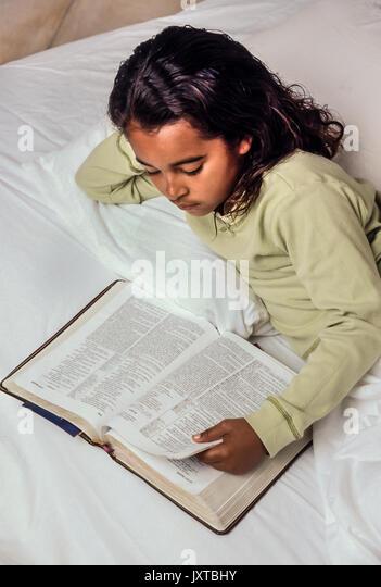 Ethnische kind Lesen der Bibel im Bett junge Mädchen 7-10 Jahre alten afrikanischen amerikanischen/Kaukasisch Stockbild