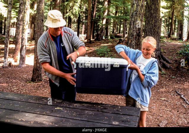 Vati und Mädchen picknicken Holz Natur Abenteuer Abenteuer Spaß miteinander Sweatshirt gerne helfen Bäume Stockbild