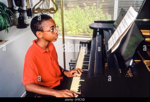 Elementare alter Junge praktizierende Praktiken Klavierunterricht musikalische Musiker © Myrleen Pearson Stockbild