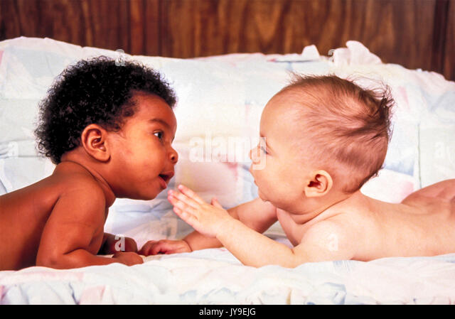 Zwei Babys liegen auf Mägen eng erreichen heraus erreichen, ihre Welt und jede andere neugierige Fragen interracial Stockbild