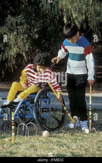 Glückliche junge behinderte Mädchen spielt Krocket Bruder Freund Jugend im Rollstuhl © Myrleen Pearson Stockbild