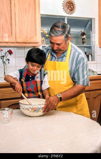 Opa Enkel Enkel help Hilft helfen niedlich Junge Kind lehre Kinderbetreuung kochen Baby- Mann mit Familie innen Stockbild