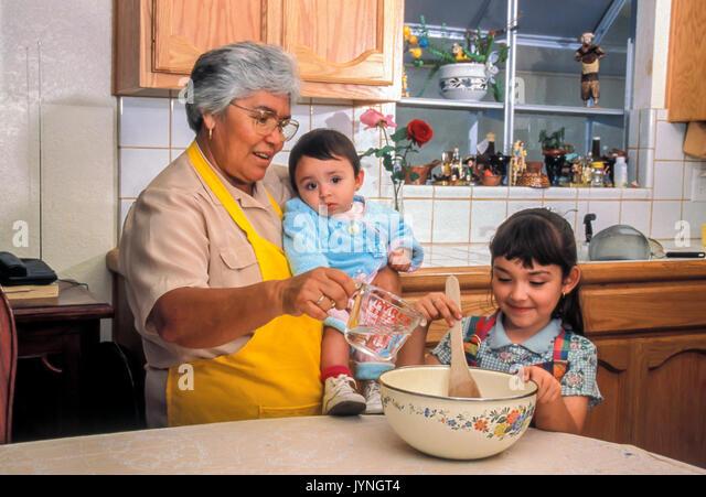 Oma Großmutter Enkelkind helfen hilft Kind helfen Lehre niedliche Mädchen arbeiten Frau mit Baby Kleinkind Stockbild