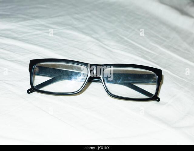 Zusammengeklappt schwarzer Brille ruht auf weißen Bettlaken; England; UK Stockbild