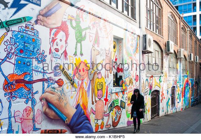 In ihrem Telefon vertieft, eine Frau geht bis AC/DC Lane, Flinders Lane, Melbourne, Australien Stockbild