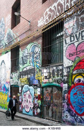 Man Walking Vergangenheit Wandmalereien in Hosier Lane, Melbourne, August 2017 Stockbild