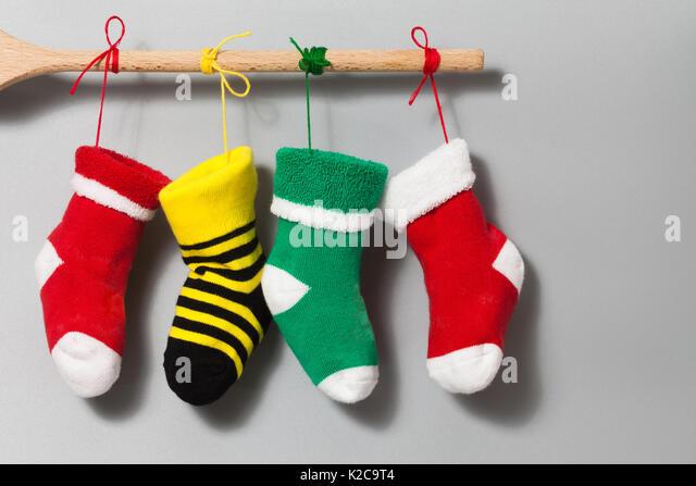 Frohe Weihnachten Text Einladungskarte. Hängende Weihnachtssocken auf grau beige Hintergrund. Bunte strümpfe Stockbild