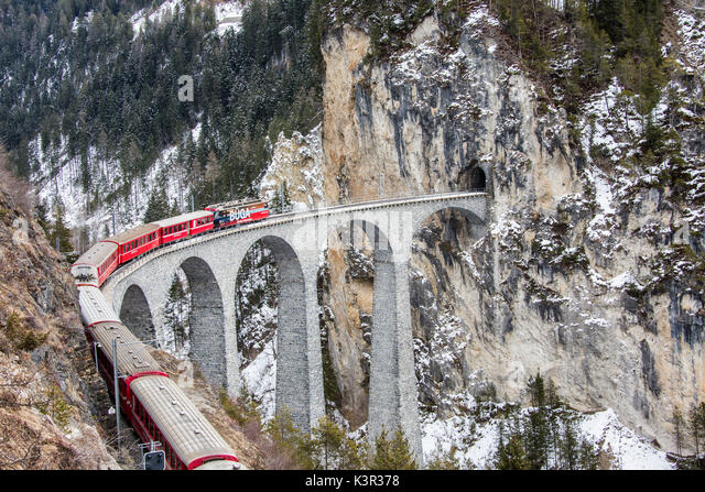 Bernina Express führt durch Landwasser Viadukt und verschneiten Wälder Filisur Kanton Graubünden Stockbild